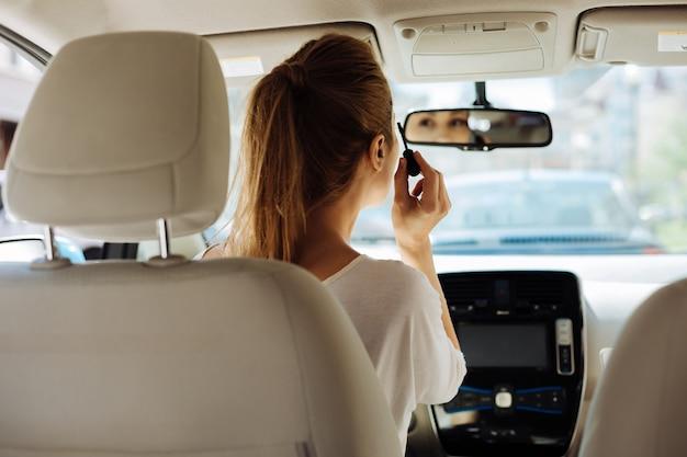 Профессиональная косметика. приятная красивая блондинка женщина держит кисть для туши и красит ресницы, глядя в зеркало заднего вида