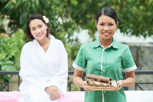 Professional cosmetologist holding tray with herbs for spa procedure