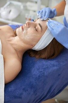 Профессиональный косметолог делает процедуры для клиента в кабинете