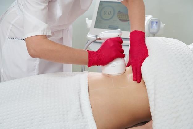 Профессиональный косметолог, выполняющий процедуру радиочастотного лифтинга на животе женщины