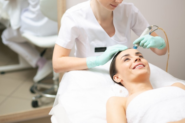 고객 가까이에 앉아서 편리한 도구를 사용하는 전문 미용사, 보습제로 얼굴 피부에 영양을 공급합니다.