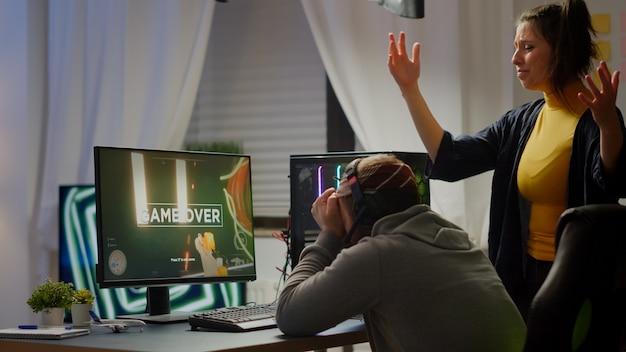 オンラインチャンピオンシップのために強力なパソコンでプレイしている一人称シューティングゲームのビデオゲームを失うゲーマーのプロのカップル。仮想トーナメント中にゲームルームで実行する悲しいサイバー