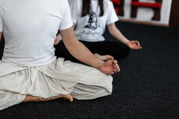 Professional couple young man and woman doing yoga in the fitness studio. close-up.