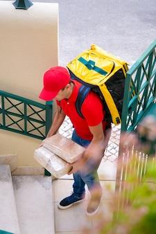 自宅で注文を配達し、エクスプレスサービスで働くプロの宅配便。赤い帽子と黄色のバックパックと箱を運ぶシャツを着ている白人の配達員。配送サービスとポストコンセプト