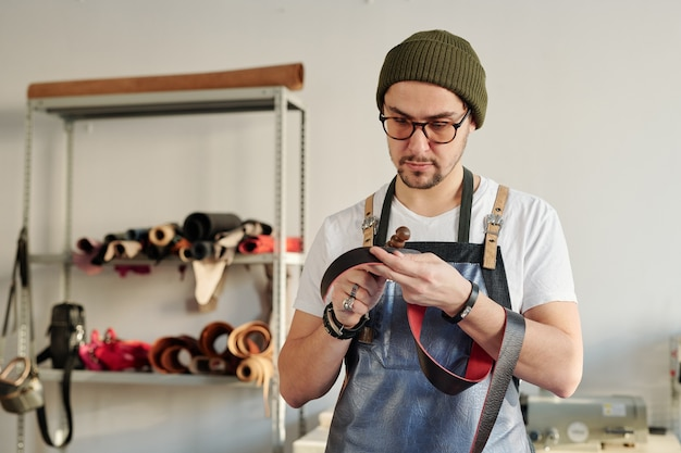 Professional craftsman in workwear holding red leather belt and wooden handtool while working over new item for client