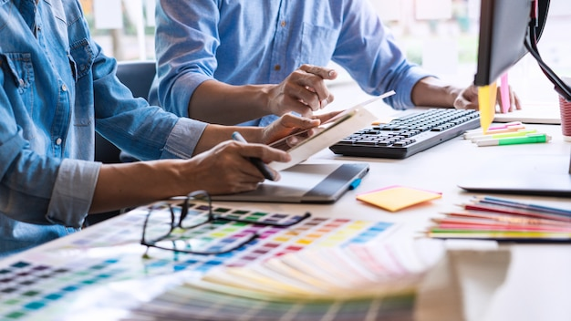 Professional creative architect graphic designer occupation choosing a color palette samples for project on office desktop computer