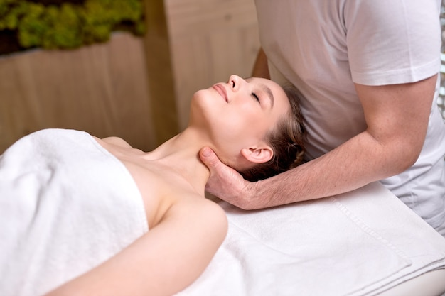 Professional cropped therapist doing healthy massage on neck and shoulders to female client