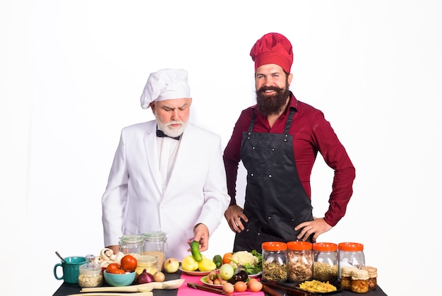 Профессиональные кулинарные бородатые повара в униформе готовы приготовить здоровую пищу шеф-повар с помощником в