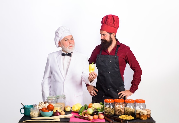 전문 요리 두 명의 요리사가 제복을 입은 수염 난 남자 요리사와 함께 테이블 근처에 서 있습니다.