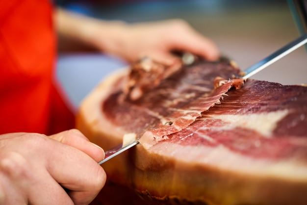 Tagliapasta professionale che intaglia fette da un intero prosciutto serrano con osso