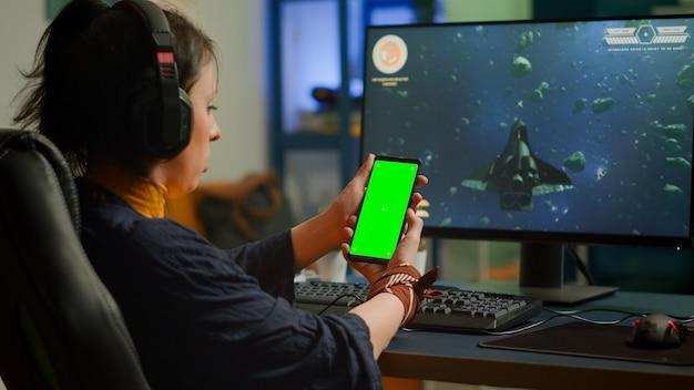グリーンスクリーン、クロマキー、強力なコンピューターでビデオゲームをプレイするデスクトップ分離ディスプレイのモックアップを備えた電話を見ているプロのサイバーゲーマー。ヘッドセットを装着したプレーヤーストリーミングシューティングゲーム