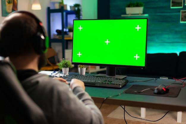 Профессиональный кибер-геймер, играющий в цифровые видеоигры на мощном компьютере с зеленым экраном. игрок, использующий пк с макетом цветного изолированного рабочего стола, потокового шутера, в гарнитуре