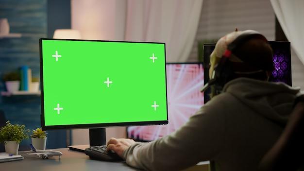 グリーンスクリーン、クロマキー、モックアップデスクトップ分離ディスプレイでビデオゲームをプレイするプロのサイバーゲーマー。ヘッドセットを装着したモックアップ画面ストリーミングシューティングゲームを備えた強力なコンピューターを使用しているプレーヤー