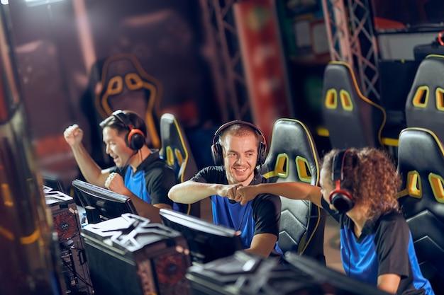 E스포츠 토너먼트에 참가하는 동안 주먹을 휘두르고 성공을 축하하는 전문 사이버 스포츠 게이머. 온라인 비디오 게임
