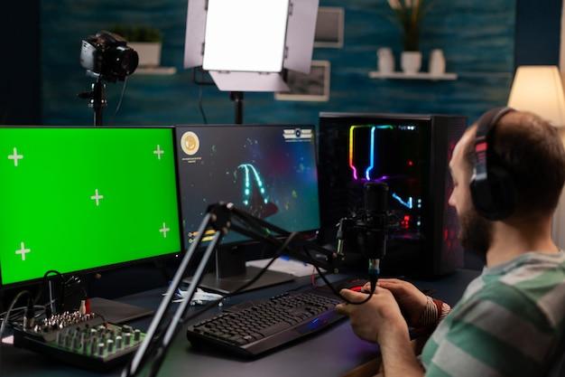 녹색 화면 디스플레이가 있는 강력한 전문 컴퓨터에서 디지털 비디오 게임을 하는 전문 사이버 스트리머. 크로마 격리 데스크탑 스트리밍 슈팅 게임을 모의로 pc를 사용하는 플레이어