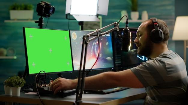 グリーンスクリーンモックアップ、クロマキーディスプレイを備えたプロの強力なコンピューターでオンラインビデオゲームをプレイするプロのサイバーストリーマー。分離されたデスクトップストリーミングでスペースシューティングゲームをプレイするゲーマー