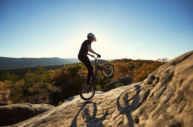 Профессиональный велосипедист, балансирующий на пробном велосипеде на закате