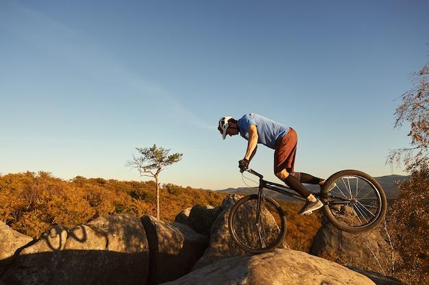 日没時に試用自転車でバランスをとるプロのサイクリスト