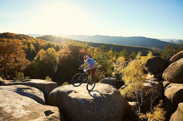 Профессиональный велосипедист, балансирующий на пробном велосипеде на закате Premium Фотографии