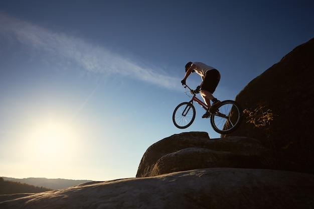 日没時にトライアル自転車でバランスをとるプロのサイクリスト
