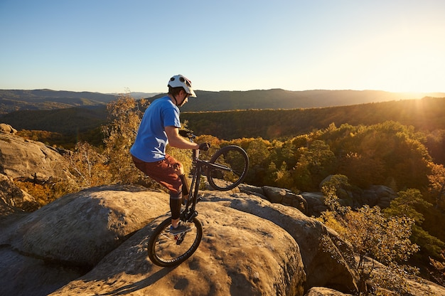 일몰 시 시험용 자전거에서 균형을 잡는 전문 사이클리스트