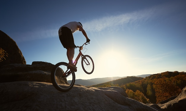 Professional cyclist balancing on trial bicycle at sunset