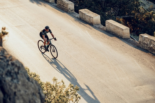 Профессиональный велосипедист на горной дороге на рассвете