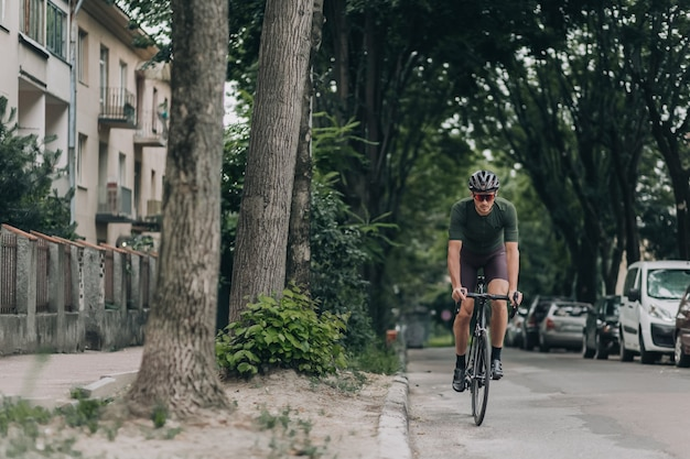 Professional cyclist in sport clothes, helmet and glasses having ride during morning time on street of old. concept of strength and motivation.