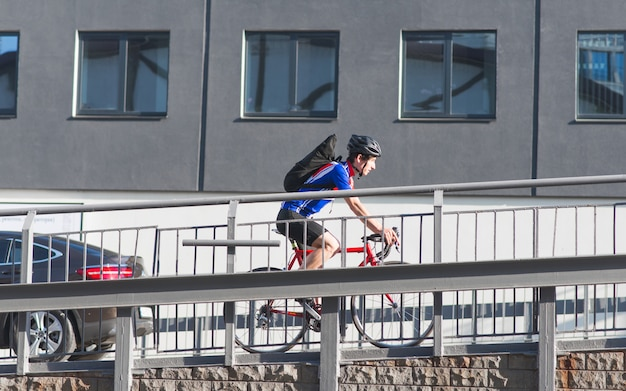 Professional cyclist in sportswear and a helmet rides a bike up the bridge over the surface of architecture