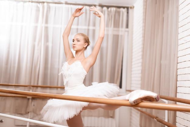 Professional dancer rehearses near ballet barre.