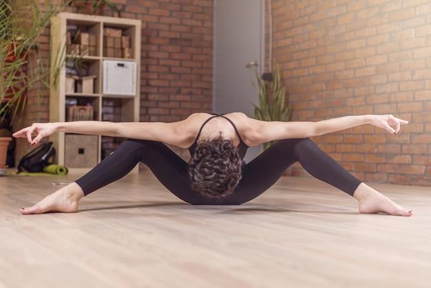 Профессиональная танцовщица сидит лицом вниз и вытягивает с раздвинутыми ногами и руками, позирует в художественной позе в студии