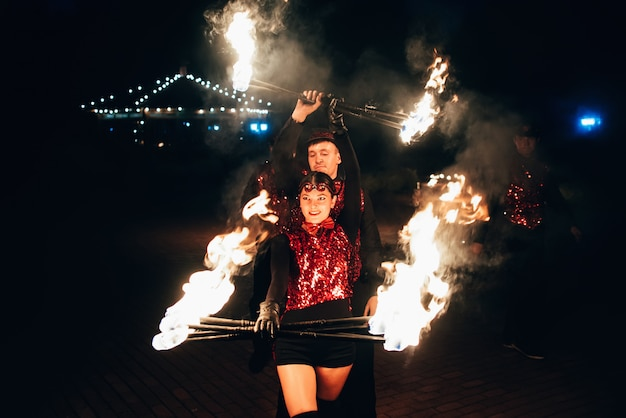Professional dancers men and women make a fire show and pyrotechnic performance