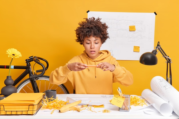 Professional dark skinned young female architect dressed in sweatshirt makes photo of her sketches on mobile phone sits at desktop