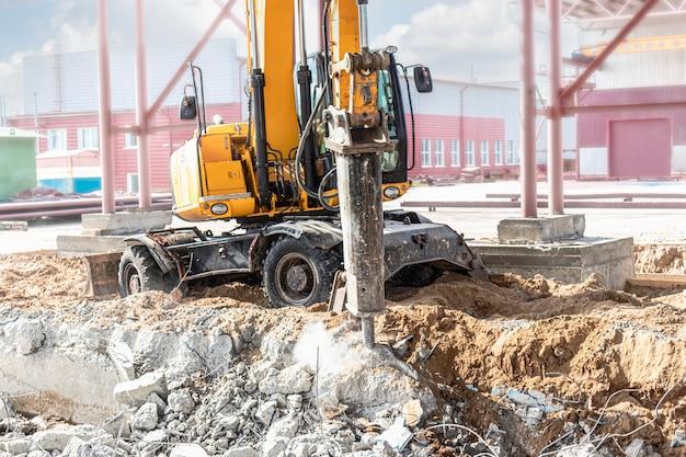 굴착기가 있는 산업용 유압 해머를 사용하여 철근 콘크리트 구조물의 전문적인 철거. 금속 피팅 막대. 콘크리트의 잔해와 부스러기.