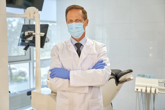Профессиональный хирург-стоматолог гордо позирует на своем рабочем месте