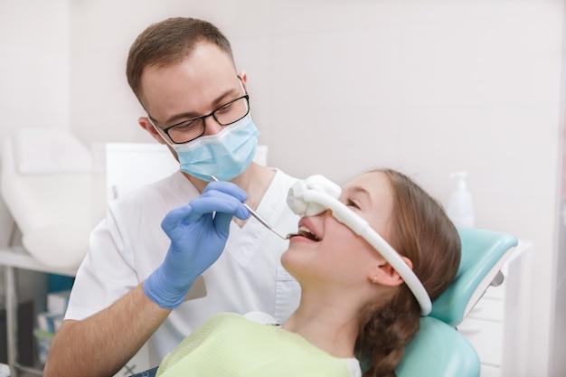 Профессиональный стоматолог осматривает зубы молодой девушки, используя на ней ингаляционную успокаивающую маску