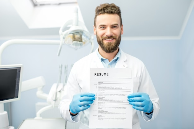 Professional dentist holding resume for a new job standing at the dental office