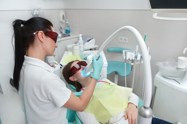 Профессиональный стоматолог работает в ее офисе, отбеливая зубы своего пациента