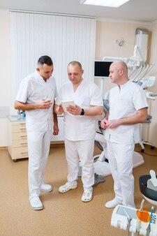 На консультацию собрались профессиональные стоматологи. стоматологический кабинет для обследования пациентов. обсуждение процесса лечения зубов у пациентов
