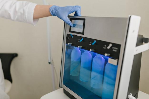 若返りのための専門的なデバイス、青いボトルの薬。ボトックス、美容、治療、手術の準備
