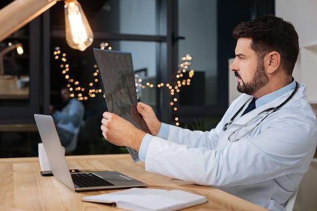 Профессиональный диагност. умный опытный красивый врач, изучающий рентгеновский снимок и ставящий медицинский диагноз, выполняя свою работу