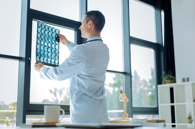 전문적인 진단. 창 근처에 서서 진단을 생각하면서 x 레이 스캔을보고 똑똑한 숙련 된 잘 생긴 의사