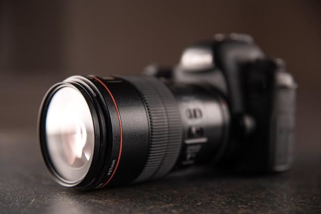 Крупный план профессиональной цифровой камеры на размытом фоне. концепция техники для работы с фото и видео.