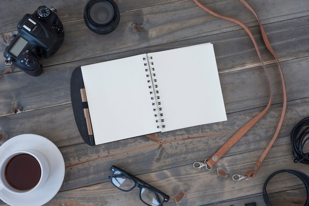 Professional digital camera; cup of coffee; blank spiral notepad; pen; spectacles and cable on wooden table