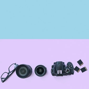 Professional digital camera with accessories and spectacle on dual background