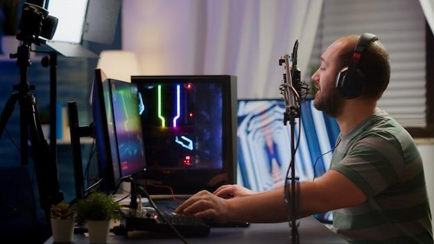 シューティングゲームのオンラインゲーム選手権のための最新のグラフィックスを備えたヘッドフォンストリーミングビデオゲームを備えたプロのデジタルプレーヤー。ゲームスタジオでオンラインゲームをプレイするミキサーでサウンドをチェックするプロゲーマー
