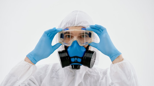 Professional disinfector looking at you through safety glasses