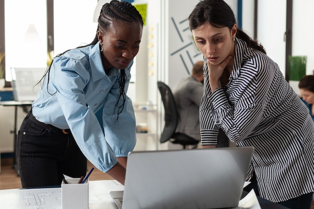 Professional diverse architect women working on laptop computer on blueprint plans for building