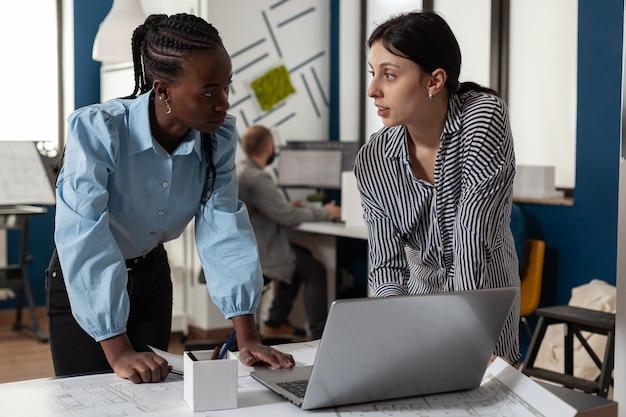 Professional diverse architect women working on laptop