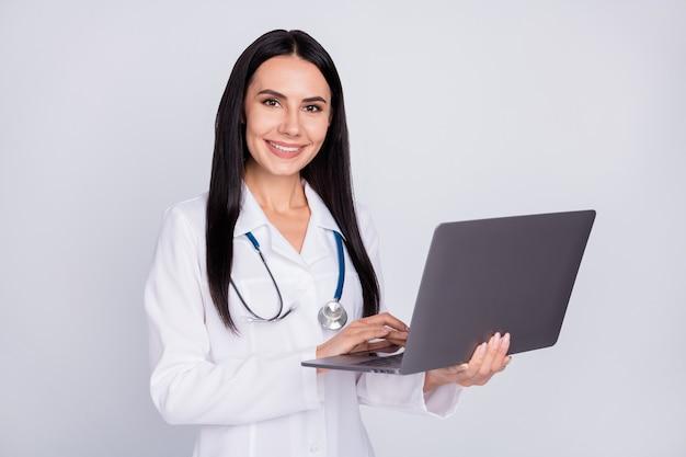 Профессиональная дама со стетоскопом в белом лабораторном халате держит ноутбук